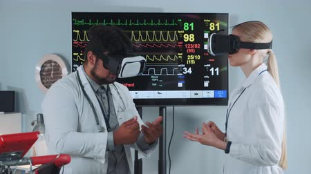 tests : Mixed race doctors in VR glasses discussing about something in modern sports lab with EKG data on display in the background.