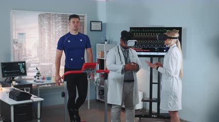 ekg : During the treadmill test two mixed race doctors in VR glasses speaking about something while athlete walking on racetrack. In Scientific Sports Laboratory. Wideo