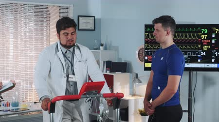есть : Doctor in lab coat showing athlete how properly walk on treadmill. There is a big display in the background. In Scientific Sports Laboratory. Стоковые видеозаписи