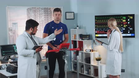 treadmill : Mixed race sports scientist explaining athlete EKG data during treadmill testing. His female colleague making notes looking on display. Scientific Sports Laboratory.