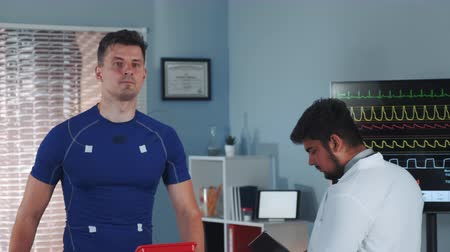 závodní dráha : Treadmill test: sportsman walking on racetrack while mixed race doctor coming to monitor the process and to make notes in big sports lab.