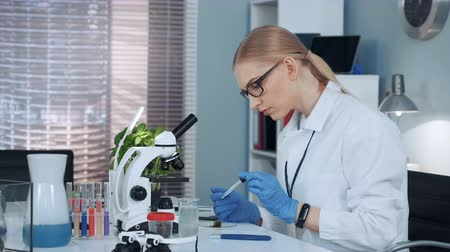pipet : Female chemistry professor in lab coat using pipette to drop fertilizers on something and doing that two times