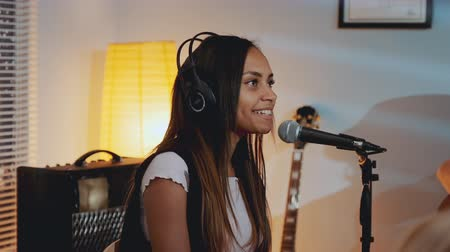 rehearsing : Close-up of beautiful smiling girl in headphone singing her favourite song on the rehearsal in home studio in the evening.