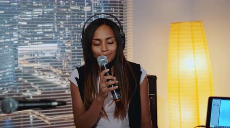 rehearsing : Close-up of beautiful multiracial girl in headphone singing into microphone and recording a song in home studio with skyscrapers in the background.