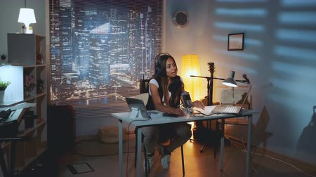 verslaggever : Home recording studio: famous black blogger recording accost to her readers, sitting in cozy home studio and speaking into the microphone in the evening. Stockvideo