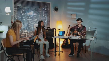 multirracial : Multiracial amateur band is rehearsing by singing playing keyboard and guitar in home studio with cozy interior in the evening