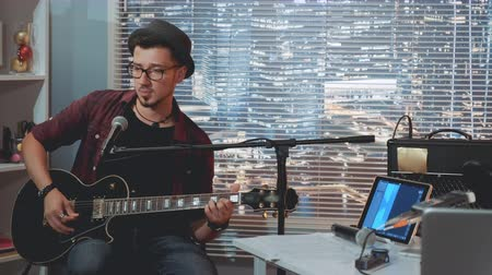 есть : Talented guitarist in hat and trendy casual clothes playing guitar and singing in home recording studio. There are skyscrapers in the background. Стоковые видеозаписи