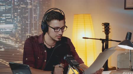 omroep : Radio news anchorman working in the evening in home studio, reading something from a piece of paper into the microphone.