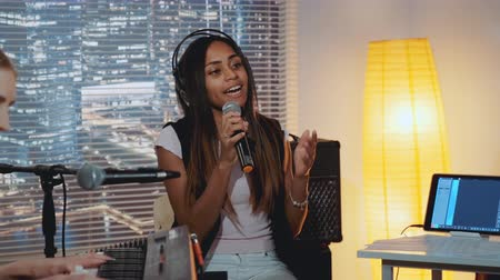 rehearsing : Home recording studio: multiracial pretty vocalist singing song into microphone while her female friend playing the keyboard Stock Footage