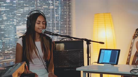 microphone : Attractive mixed-race girl emotionally singing into microphone in home studio with musical equipment in the background. Evening rehearsal.