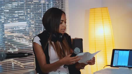 multirracial : Female black vocalist finding mistakes in musical notes of the song during rehearsal in home recording studio. She singing into microphone with a piece of paper in her hands. Vídeos