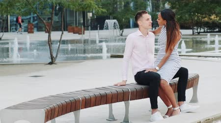 kolano : Panning shot of a beautiful multiracial couple spending time together in a romantic place outdoors. Black woman sitting on boyfriends knee and talking to him. Wideo