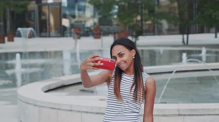 selfie girl : Cheerful african girl taking selfie in front of fountains in city centre. She is smiling and changing poses. Stock Footage