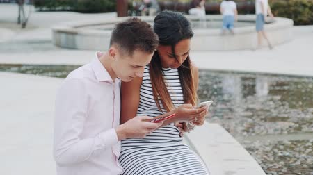 multirracial : Multiethnic couple sitting together outdoors and looking in the smartphones. They not talking to each other. Vídeos