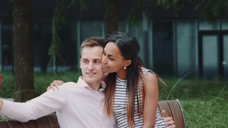 multirracial : Romantic multiethnic couple sitting on bench in park and taking selfie. They smiling to the camera.