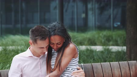 multirracial : Romantic mixed-race couple hugging and stroking each other outdoors. They having date in a beautiful city park.