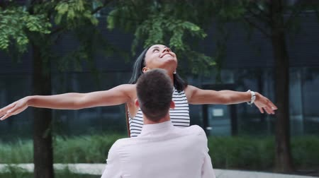 multirracial : Beautiful black girl raising hands up like flying bird while boyfriend spinning her around outdoors. She is in the seventh heaven from happiness.