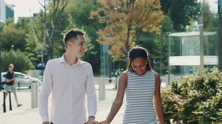 multirracial : Multi-ethnic couple shyly looking at each other while walking the street, holding hands and talking. Relationship concept. Vídeos