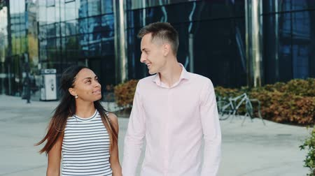 multirracial : Smiling black girl having a date with her boyfriend in the city center. They holding hands, walking and talking to each other.