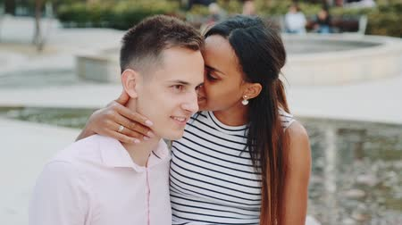 тишина : Pretty black lady whispering something in boyfriends ear and then showing keep silence gesture to the camera with point finger and mouth. She telling him some special things.