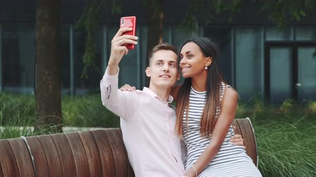 multirracial : Cheerful young couple taking selfie sitting on bench outdoors. They spending their time in big park. Vídeos