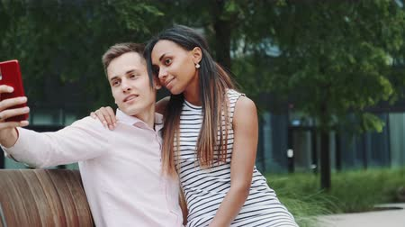 multirracial : Close-up of multiracial girl and boy in love hugging and taking selfie. They sitting on bench in big city park.