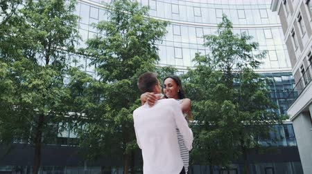 multirracial : Happy young man spinning around beautiful black woman in park. They are in love and having a special time together.
