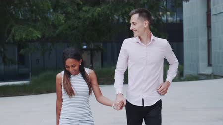 multirracial : Two mixed-race sweethearts having fun running together in park. They taking hands together and smiling.