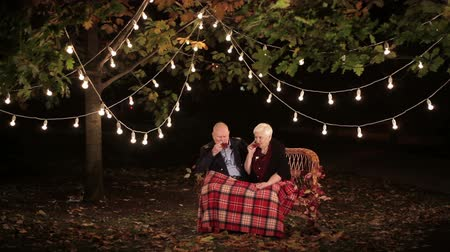 gyakorló orvos : elderly couple in love talking to each other and drinking tea Stock mozgókép