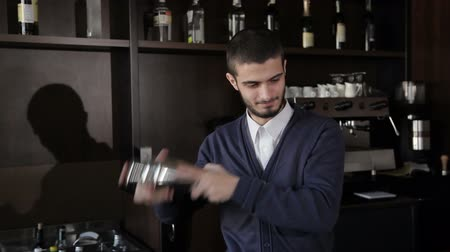 straining : Barman makes cocktails with a shaker.