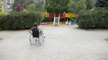 специальный : A girl with a broken leg in a wheelchair in front of the playground Стоковые видеозаписи
