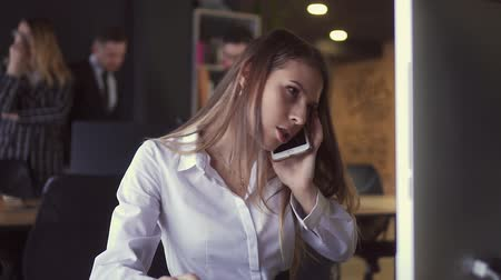 gaining : Girl Talking on the phone at the computer in the Office Stock Footage