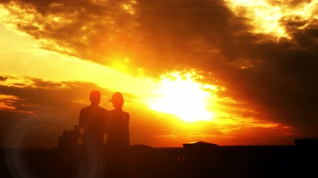Couple walking on summer evening embankment. Beautiful evening sunset sky.