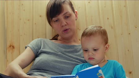 Young mother and her son are reading book.