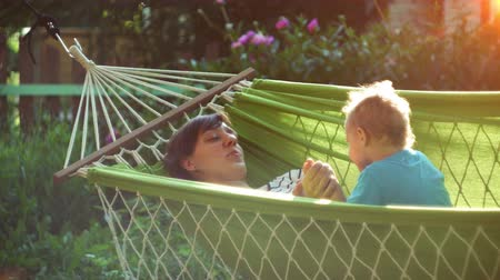 Happy mother and her two years old baby boy lying in hammock