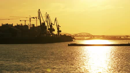 Timelapse with silhouette of tanker on industrial port and sunset background