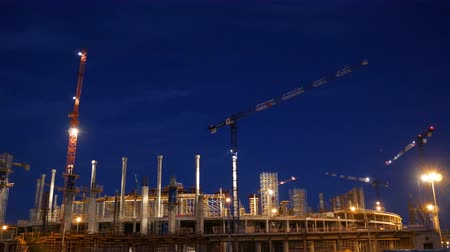 Timelapse with cranes working on construction site on night sky background. Concept of working construction yard. Wideo