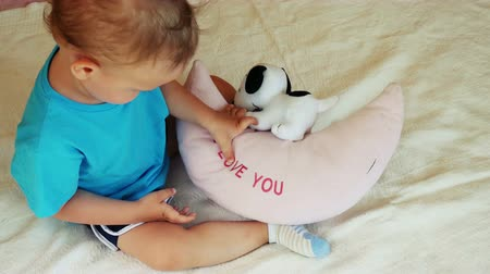 toco : Two years old boy sitting on bed and reading sign I LOVE YOU and smiling. Vídeos