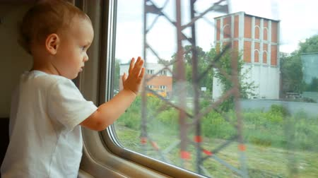 A little baby boy looking in the train window Wideo