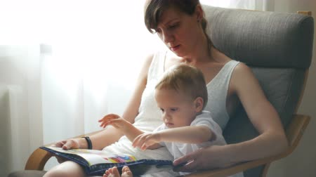 мама : Mother and her two years old baby boy are reading book sitting in armchair in sunny room Стоковые видеозаписи