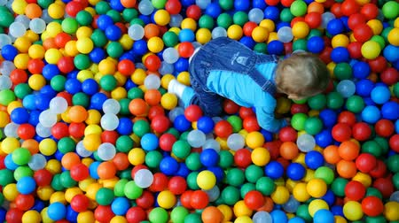 A little baby boy sliding on slide in a ball pool. Wideo