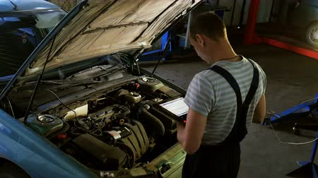 Mechanic in a auto repair shop checking engine using a digital tablet Wideo