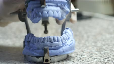 Closeup of a dental technician making of denture in a dental lab.