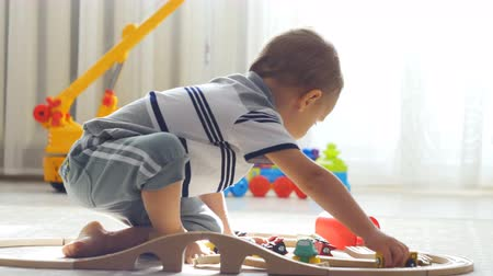 Two years old boy plays with wooden railroad in a sunny room.