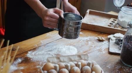 sifting : Sifting flour through sieve. Women hands sifting flour on a table. Cooking and backing preparation.