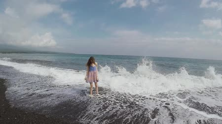 volkanik : The wave breaks down on the shore and large sprays fly over the girl in black sand beach Stok Video
