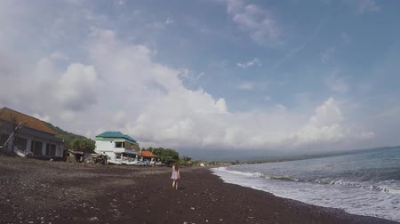 cinematic : A girl in the distance walks barefoot on a beautiful black beach of volcanic sand