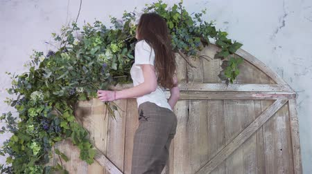 eukaliptus : Professional girl florist ascends the ladder with eucalyptus branches in her hands and decorates flowers on the beautiful wooden gate