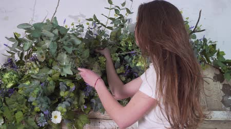 decorating : Female florist stands at a height with eucalyptus branches in her hands and decorates flowers on beautiful wooden gates Stock Footage