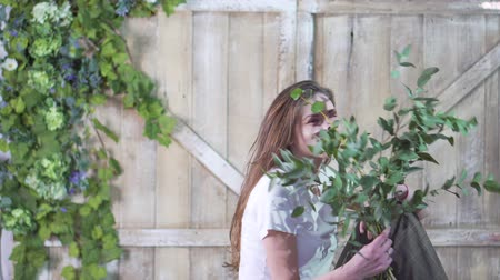 eukaliptus : Portrait of a beautiful florist girl with a eucalyptus branch against a wooden gate decorated with flowers